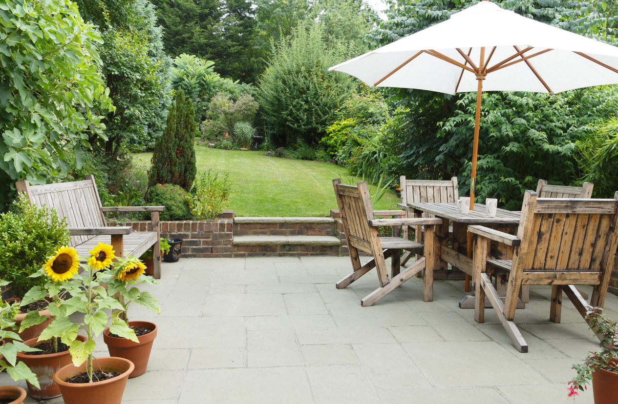 Brick patio with plants, a wooden table and umbrella with steps to a yard with green grass