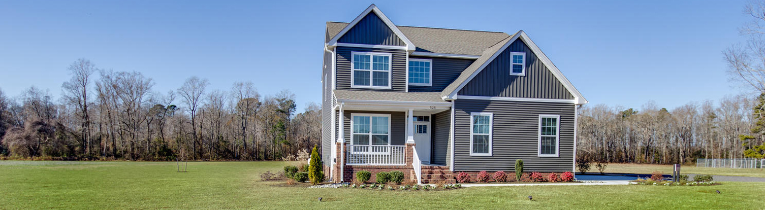 The Augusta floor plan by AB Homes with dark tan siding, white trim and landscaping wide shot