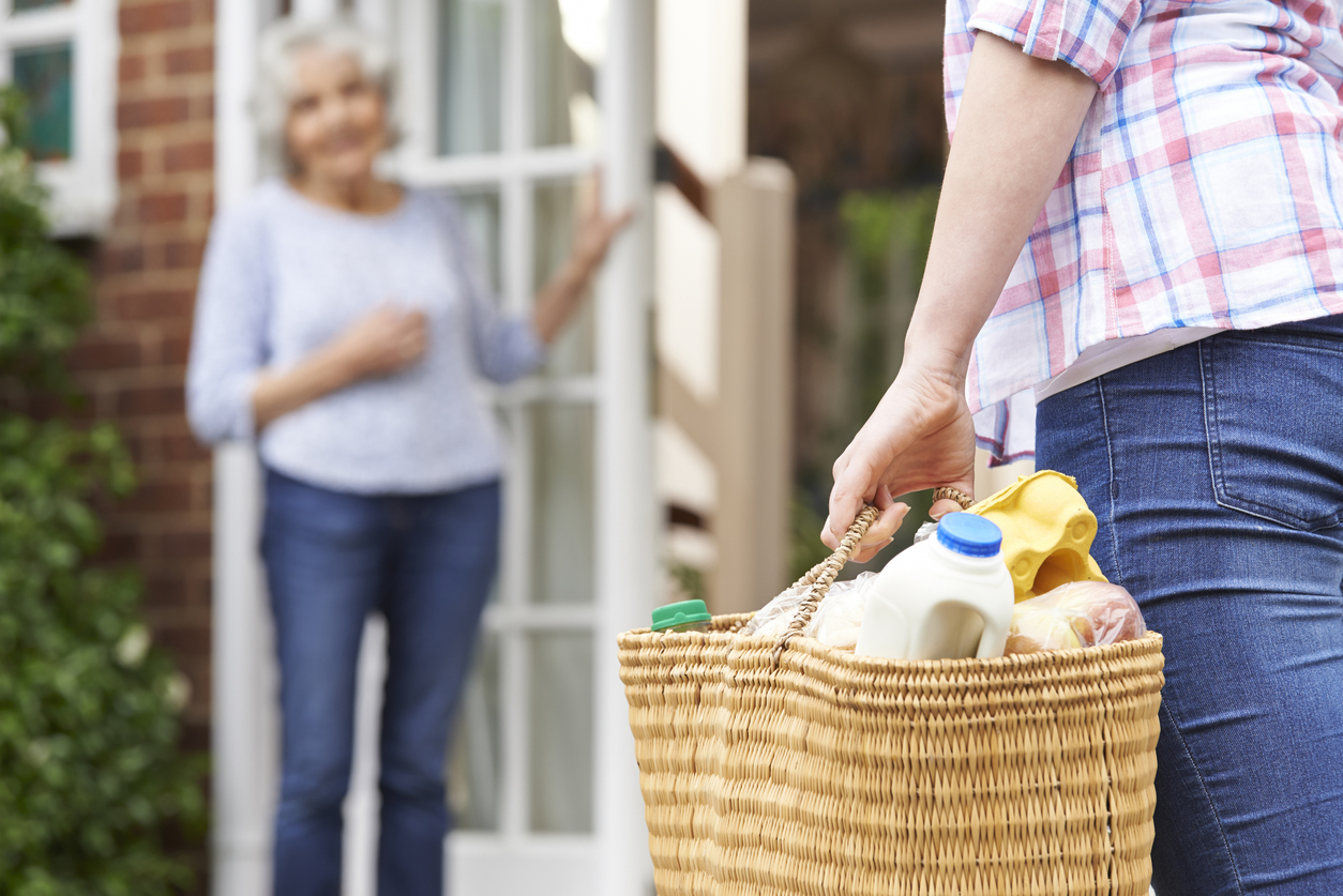 Person Bringing A Basket Of Groceries To An Older Woman