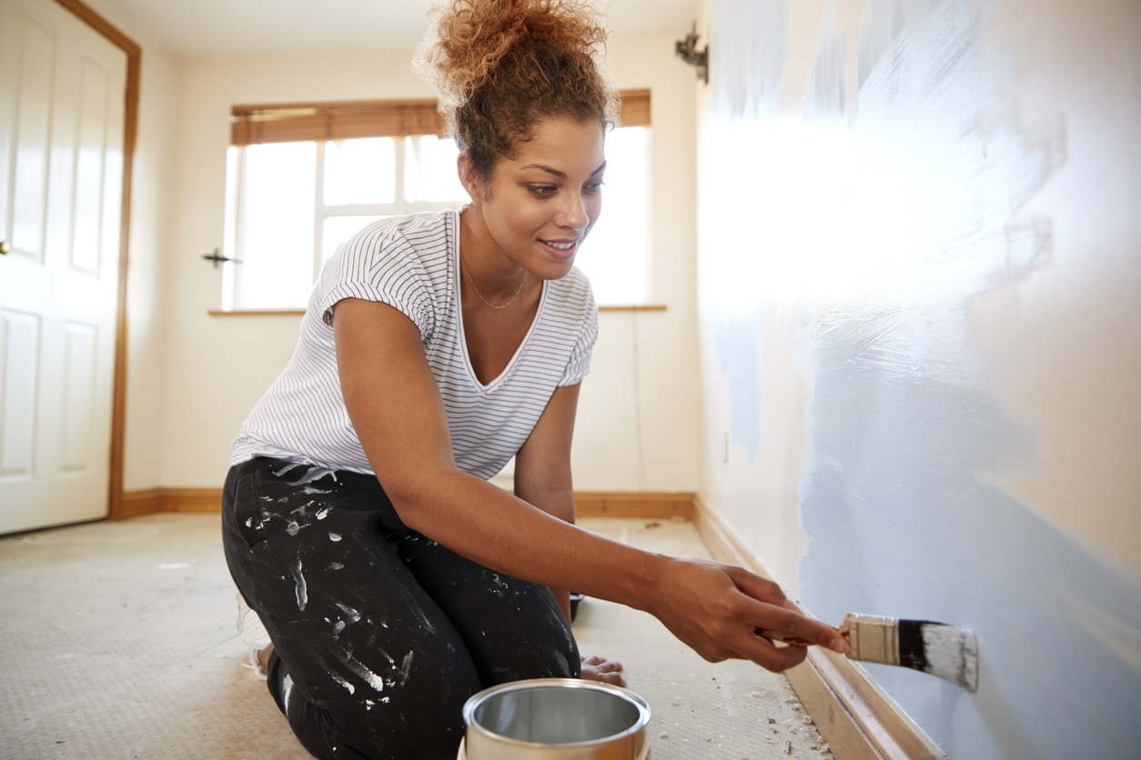 African American woman wearing a t-shirt and pants kneeling down painting a wall blue on the Preparing your home for resale blog