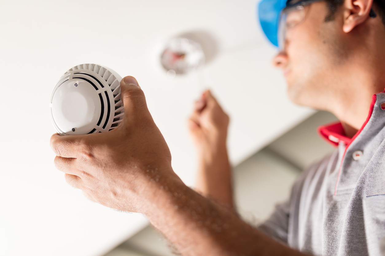 Man installing a smoke detector wearing a gray shirt and blue hat on AB Homes' blog 7 Safety Features Every Home Should Have