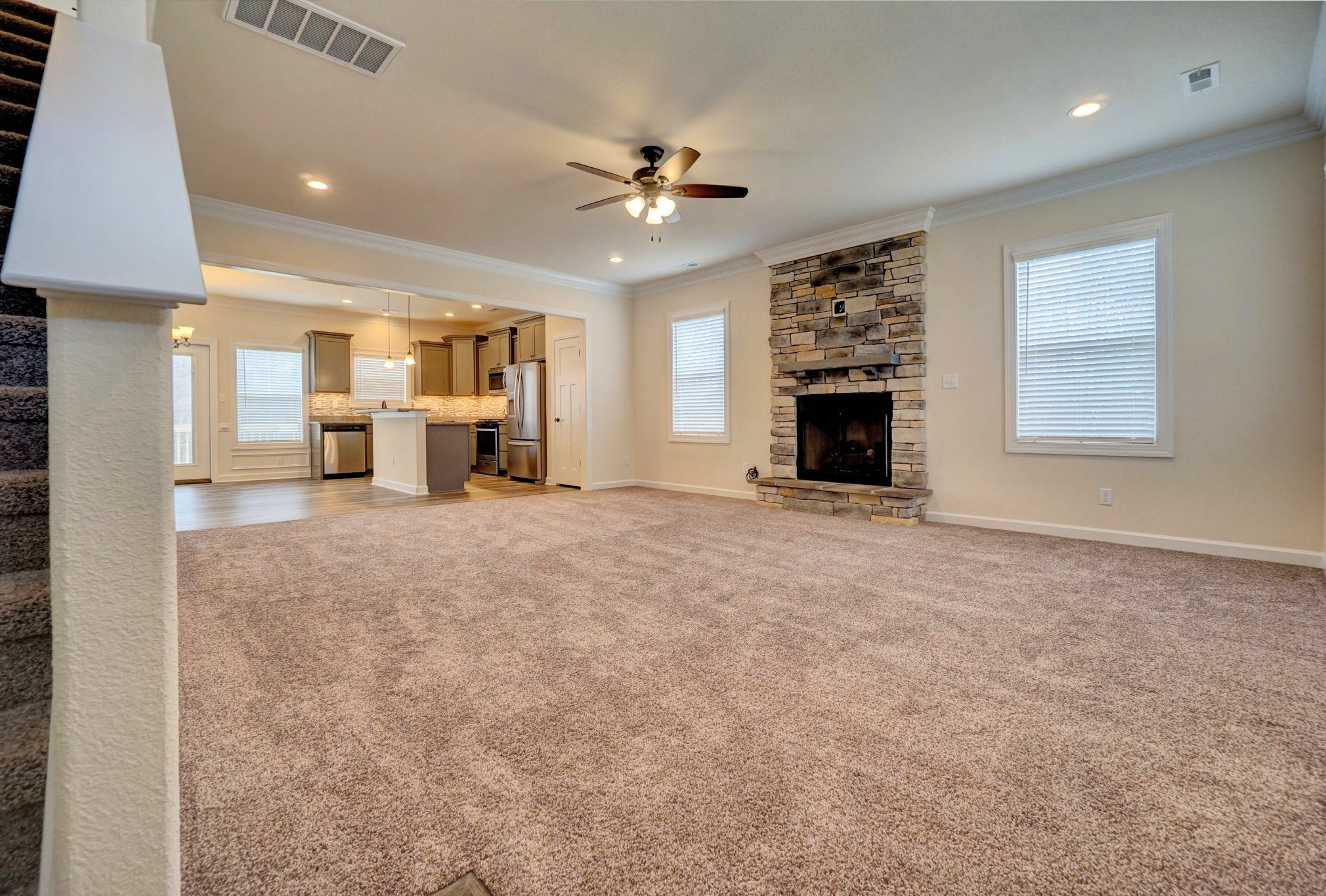 AB Homes The Kitty Hawk floor plan living room, stone fireplace and kitchen