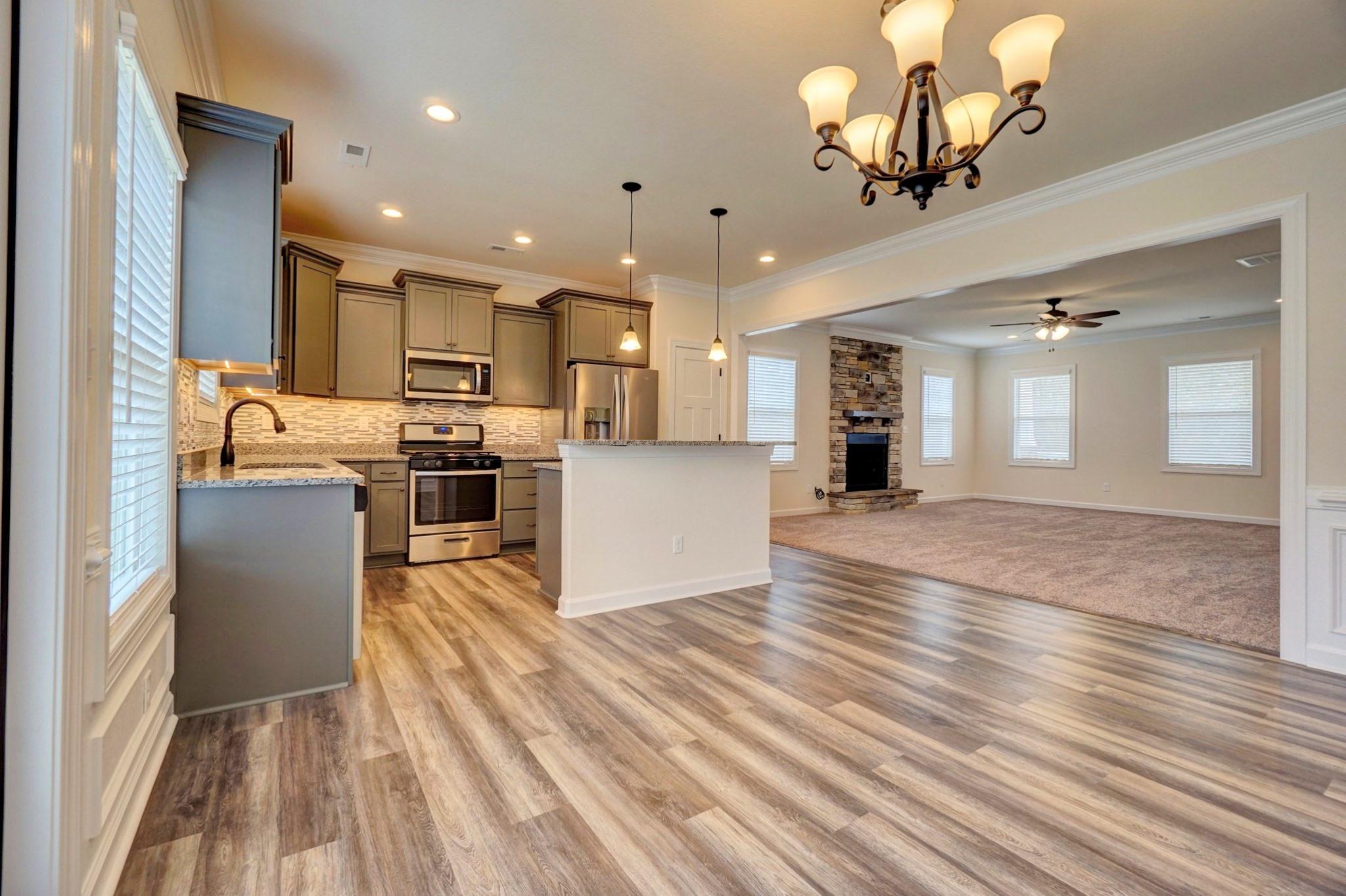 AB Homes The Kitty Hawk floor plan living room, stone fireplace and kitchen with stainless steel appliances