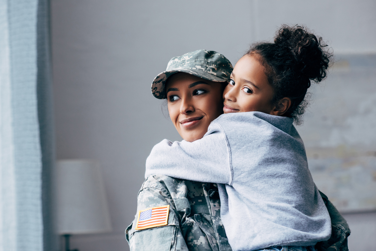 Smiling African American soldier in military uniform holding daughter on arms at home on the AB Homes blog AB Homes is Military Proud