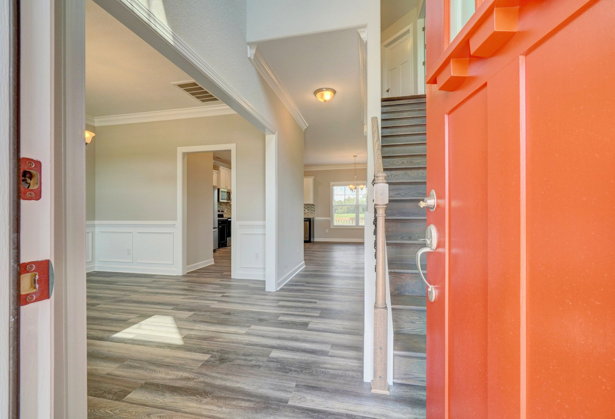 AB Homes The Holland floor plan orange front door open to the dining room and stairs on the blog The Top Five Myths about Building a Custom Home
