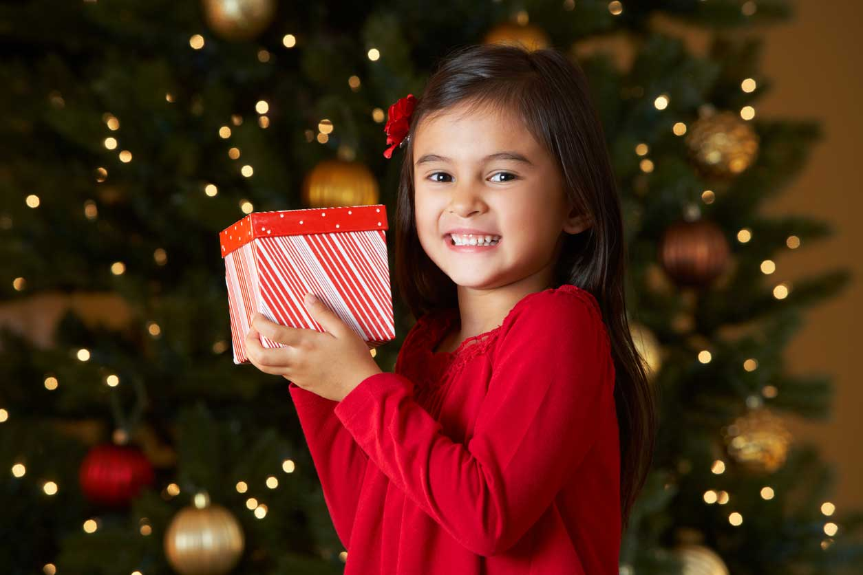 Little Girl Holding A Red And White Wrapped Package In Front Of A Christmas Tree For The ForKids Toy Drive For Hampton Roads Families