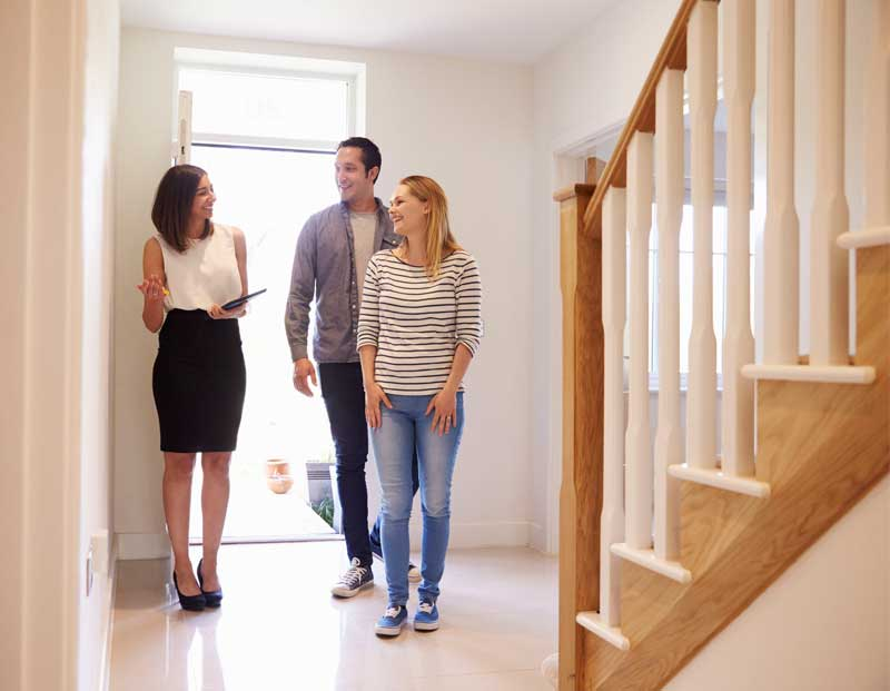 A real estate agent showing a couple a custom-built home
