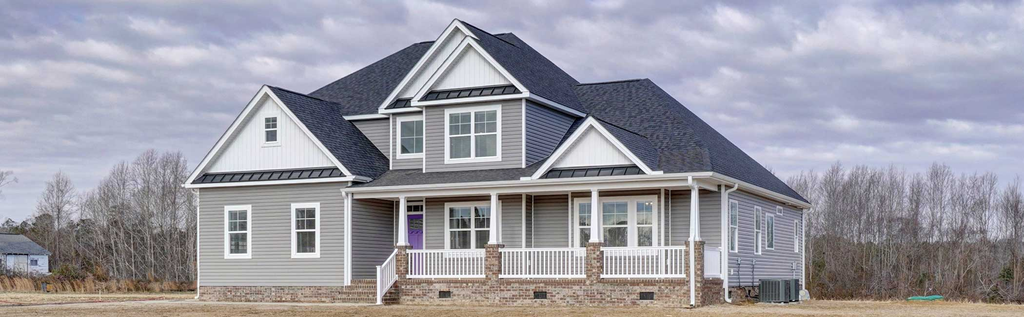 The Sussex floor plan by AB Homes with gray siding white trim and purple door