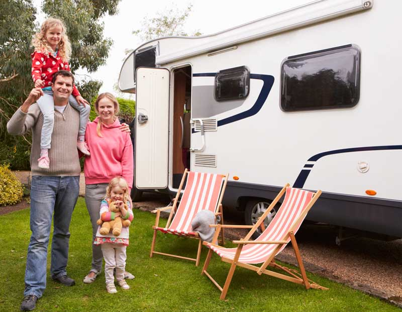 A family standing next to their RV