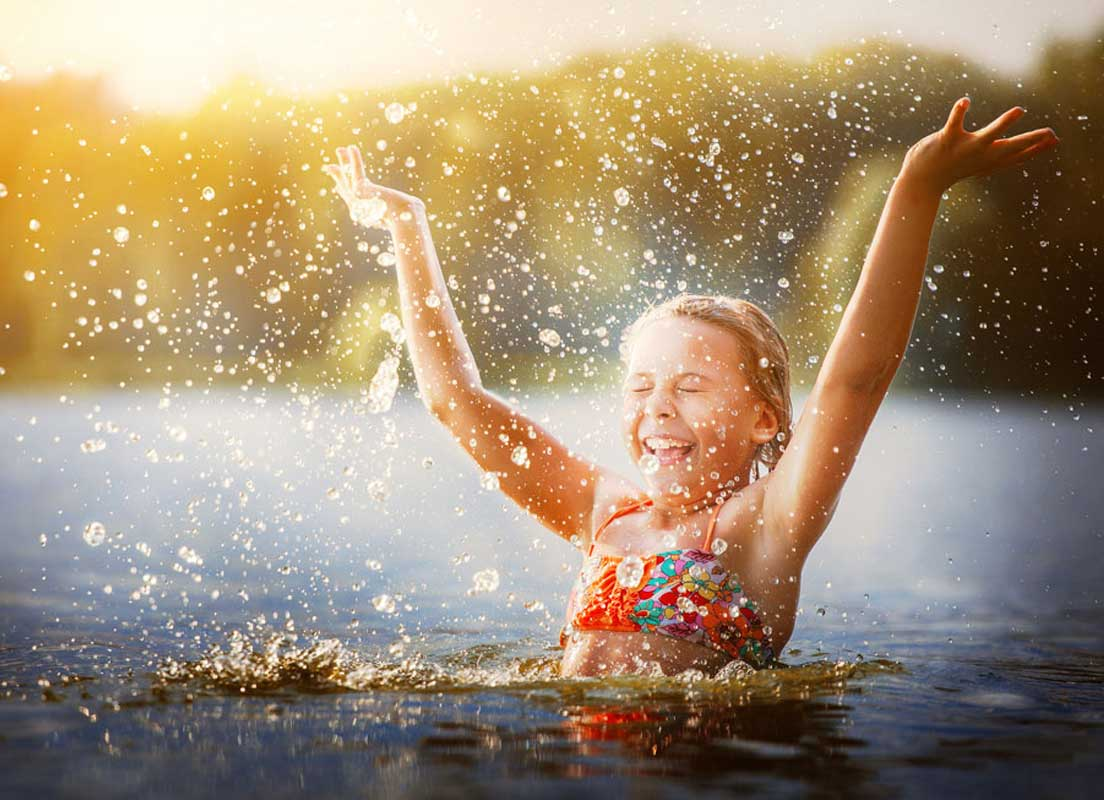 Young Girl Swimming And Splashing In A Lake In Summer In Suffolk