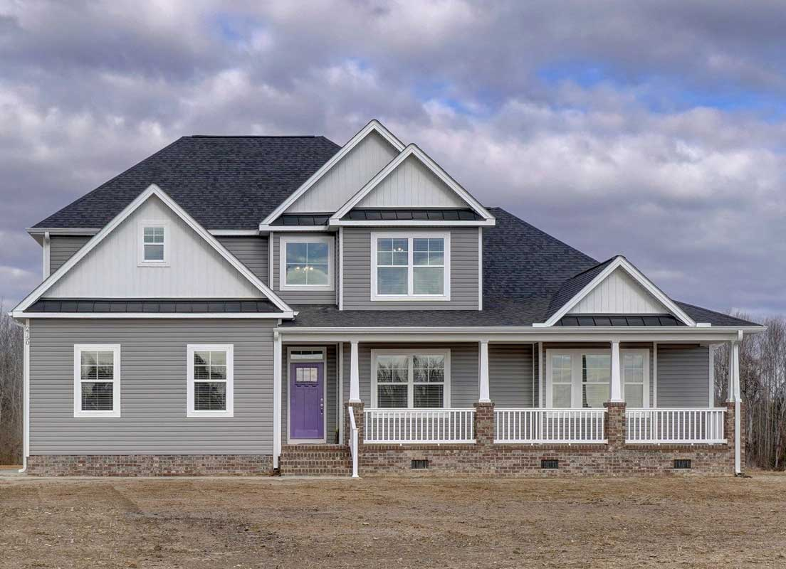 Front Picture Of The Sussex Floor Plan With Tan Siding, White Trim And A Purple Front Door By AB Homes VA