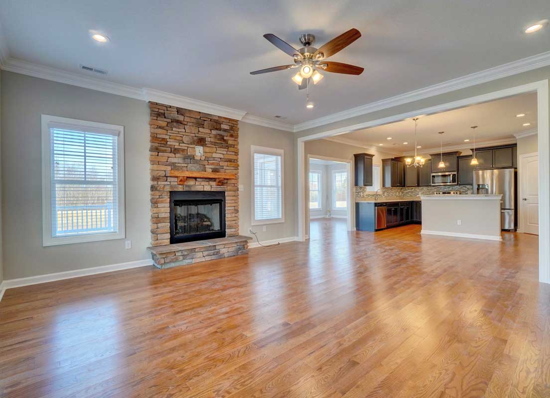 The Family Room And Kitchen With A Stone Fireplace And Stainless Steel Appliances In The Sussex Floor Plan By AB Homes VA